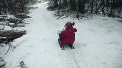 Yong girls sledging down hill Stock Footage