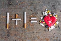 Antismoking background. Diseased heart and pills - stock photo