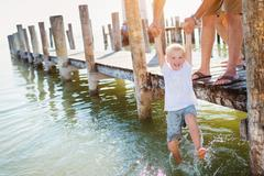 Father on the pier holding son above water, sunny summer Stock Photos