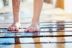 Detail of childs wet feet on pier, sunny summer day Stock Photos
