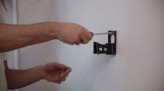 Man installs the holder bracket  on the wall - stock footage