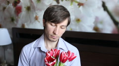 Handsome man looking at flowers - tulips and presents them in the camera Stock Footage