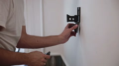 Man installs the holder bracket  on the wall Stock Footage
