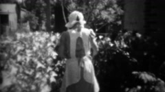 1933: Women watering garden with finger over hose end. Stock Footage