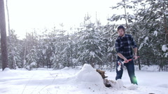 Lumberjack chopping ax to cut firewood in the winter forest Stock Footage