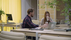 Two staff members sit in the office and drinking your morning coffee. Stock Footage
