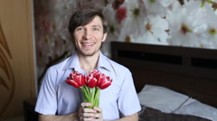 Beautiful man with affection presents flowers to the camera - the tulips. Stock Footage