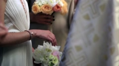 Godmother puts a ring on bride's finger during religious ceremony Stock Footage