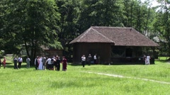 Group of wedding guests sit next to a house and photographing on grass 38 Stock Footage