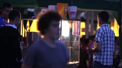 Man waiting in a popcorn stalls command that gave it while people walked Stock Footage