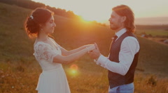 Young couple embracing and whirling at sunset Stock Footage