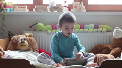 Cute little boy,sitting in bed in kids room, playing on tablet happily, stuff - stock footage