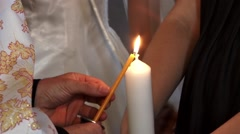 Priest lights a candle yellow then one big white held by a woman during - stock footage