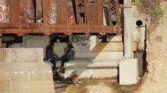 Teen girls doing drugs under a bridge. Stock Footage
