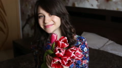 beautiful girl to sniff flowers, looking at the camera, smiling, flirting. - stock footage