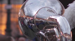 Reflected image of fanfare dressed in blue, seen in a shiny brass blowing  - stock footage