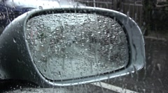 Through the rearview mirror of a car, watered cold summer rain are seen - stock footage
