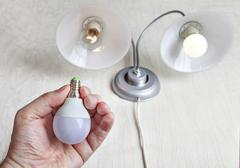 Replacing incandescent lamp in favor of LED. - stock photo