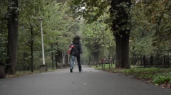 Woman with a bag on his shoulder going rushed into the alley of a park with Stock Footage