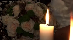 Yellow candles burning next to a bouquet of roses held by a female hand Stock Footage