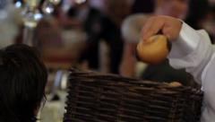 Waiter put bread on the table pieces, at each guest who is at the table in Stock Footage