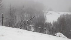 Wind blow snow on the ground at the edge of the pasture enclosed by a wooden Stock Footage