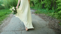 Woman in a wedding dress with a bouquet goes on the road Stock Footage