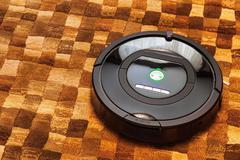 Robotic vacuum cleaner on carpet - stock photo