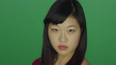 Young Asian woman turns around and stares at the camera Stock Footage