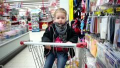 Little girl sits in a basket among the supermarket trade rows hypermarket - stock footage