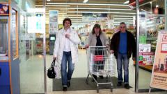 Shoppers with carts go through the doors of a large store of consumer good Stock Footage