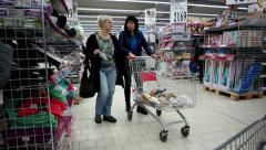 Consumers are walking among rows of supermarket buying daily use products - stock footage