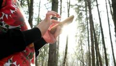 girl's hand picking up a message in the woods opposite the sun contrast - stock footage