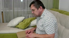 Blind white middle-aged man reading a book in Braille on the couch Stock Footage