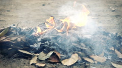 Fire, burning paper on ground, super slow motion 240fps - stock footage