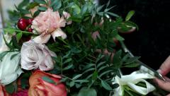 Florist adjusts his bow from a beige ribbon on a bouquet of flowers Stock Footage
