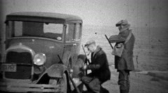 1933: Men preparing hunting shotguns at Ford model A car. Stock Footage