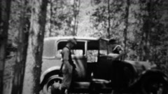 1934: Couple packing Ford model A car in deep wooded forest. Stock Footage