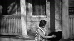 1934: Women plays with black dog on front stoop house porch. Stock Footage