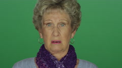Older woman looking shocked and appalled, on a green screen background Stock Footage