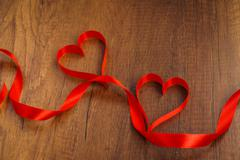 Red ribbon hearts on wood background For Valentines day - stock photo
