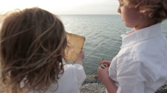 Boys Looking At Treasure Map By The Ocean Stock Footage