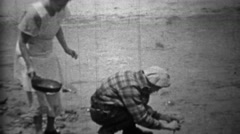 1935: Man cleaning fish creekside while wife brings frying pan. Stock Footage