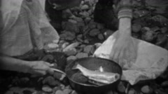 1935: Man cutting heads off sih putting into cast iron frying pan. - stock footage