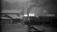 1934: Dirty smoky locomotive train passing small mountain town. - stock footage