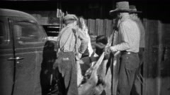 1935: Men tie dead hunted deer to front of Plymouth car for transport. - stock footage