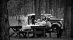 1935: Family picnic in pine tree forest at new black Plymouth car. Stock Footage
