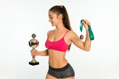 Happy fitness woman holding medal and cup isolated Stock Photos