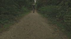 Aerial of a young woman walking through a forest, very low altitude Stock Footage