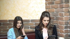 Girls sitting in cafe , sharing news with smartphone - stock footage